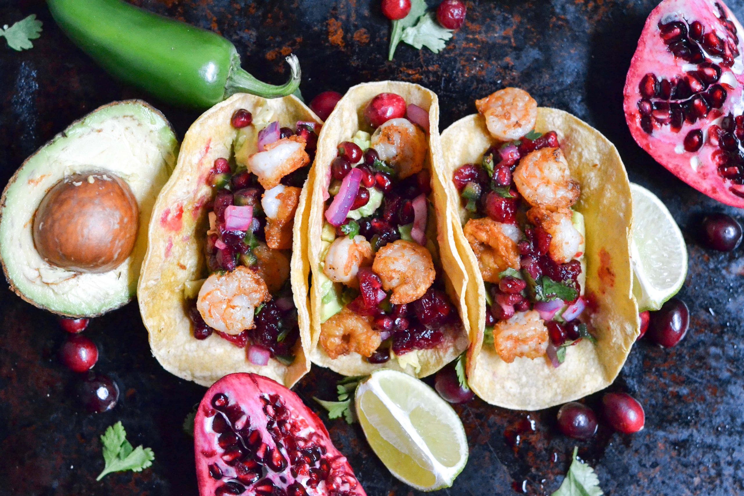 Three shrimp tacos on a baking sheet with pomegranate, avocados, and limes.