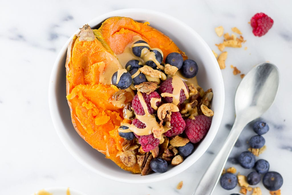 Baked Sweet Potato Breakfast Bowl with Berries - White bowl with baked sweet potato topped with creamy almond butter, fresh raspberries and blueberries and paleo granola including coconut, cashews, almonds, sunflower seeds, cinnamon and coconut oil