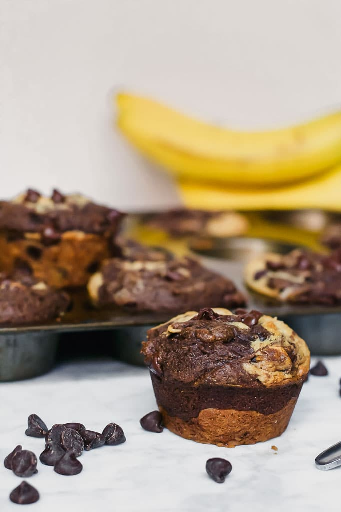 chocolate peanut butter banana muffins in a muffin tin with a spoonful of peanut butter, a bunch of bananas and scattered dark chocolate chips on a marble table - gluten-free, vegan, dairy-free swirl muffin