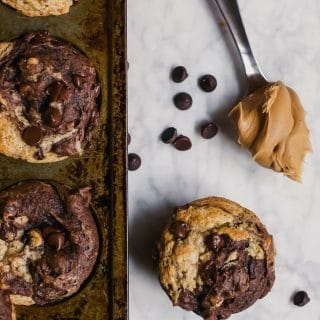chocolate peanut butter banana muffins in a muffin tin with a spoonful of peanut butter and scattered dark chocolate chips on a marble table - gluten-free, vegan, dairy-free swirl muffin