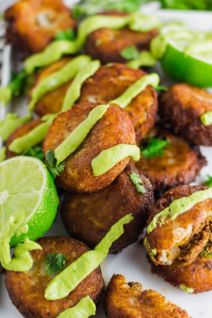 Fried mashed potato patties stuffed with taco seasoned ground beef and topped with avocado cream and fresh chopped cilantro on a white rectangular platter with fresh limes - fried potato and beef taco croquettes