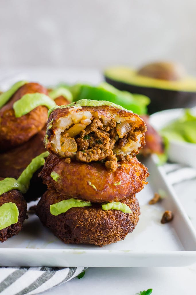 Fried mashed potato patties stuffed with taco seasoned ground beef and topped with avocado cream and fresh chopped cilantro on a white rectangular platter with fresh limes - fried potato and beef taco croquettes - gluten-free and dairy-free