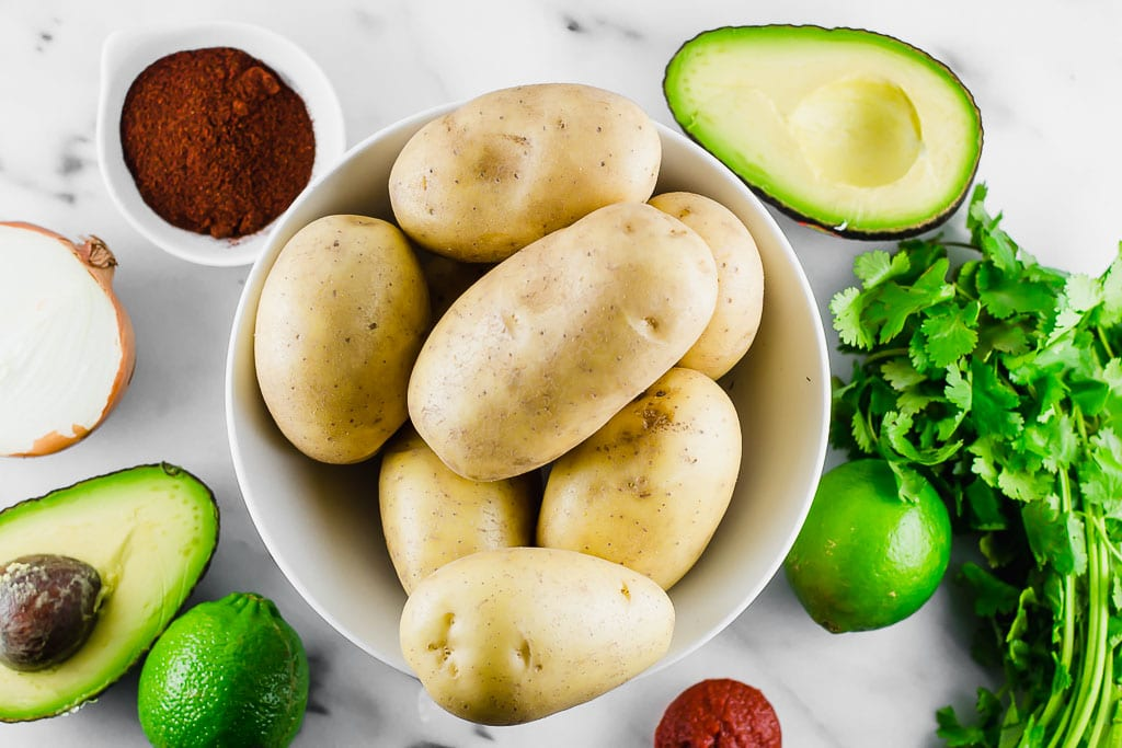 white potatoes in a bowl surrounded by avocado, lime, cilantro, taco seasonings, tomato paste
