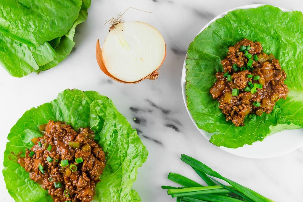 Sloppy Joe Lettuce Wraps - two gluten-free dairy-free sloppy joe lettuce wraps sitting on a marble table with fresh green onions and yellow onion and a pile of lettuce leaves - the ground beef is flavored with mustard, tomato sauce, tamari sauce, brown sugar, apple cider vinegar and topped with fresh chopped green onion