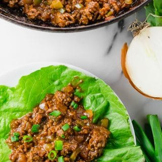 Sloppy Joe Lettuce Wraps (GF, DF) - ground beef flavored with tomato sauce, tamari sauce, mustard, apple cider vinegar, brown sugar cooked and sitting on top of a large green lettuce leaf topped with chopped green onion for serving and some ground beef in a skillet