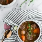 Whole30 Slow Cooker Beef Stew - a bowl of beef stew filled with red potatoes, carrots, and pearl onions in a dark beef broth in a white bowl topped with a sprig of fresh thyme sitting on top of a marble table with a white and blue striped napkin, a gold spoon, fresh herbs. Another bowl of beef stew in the top left corner.