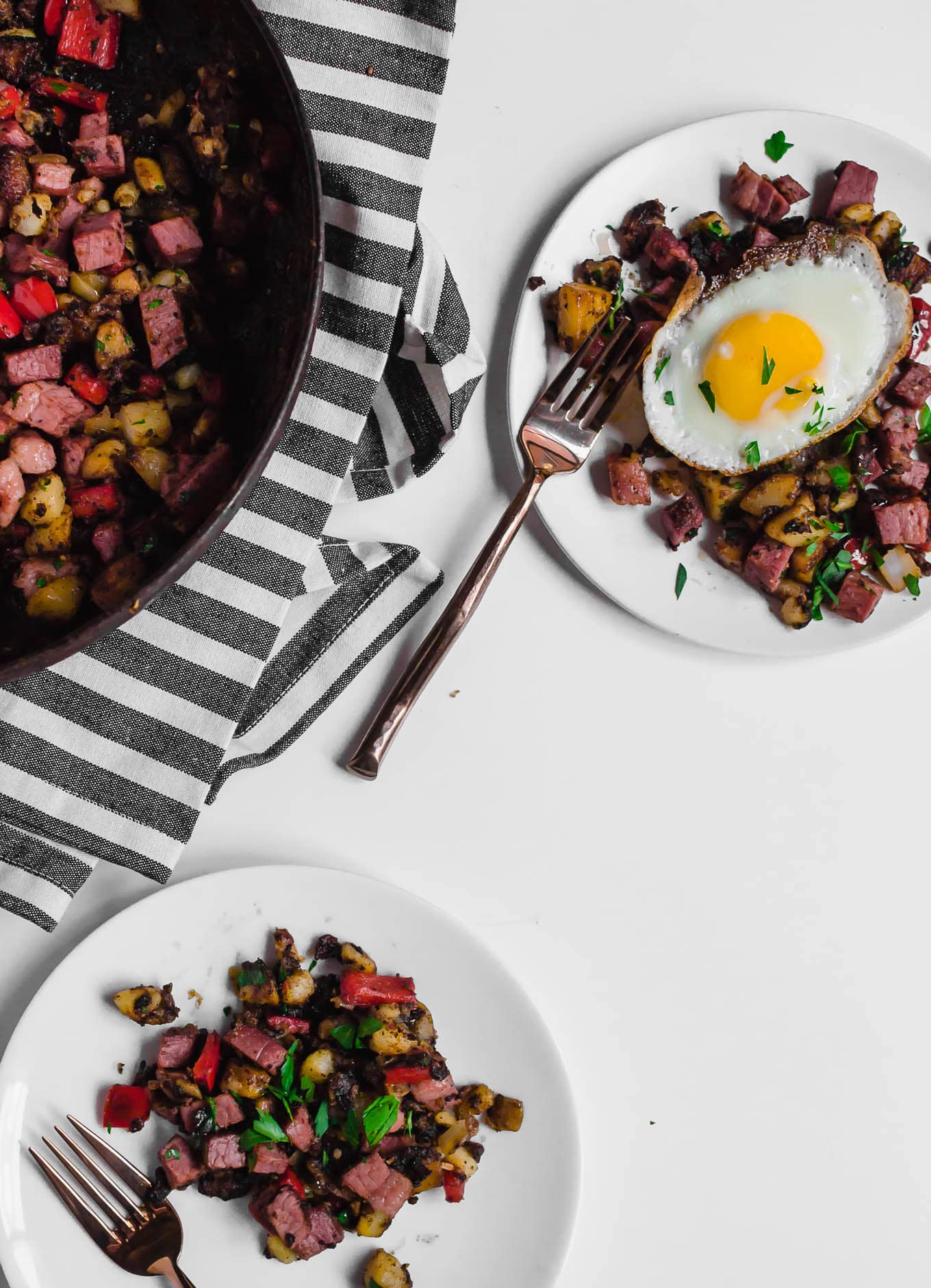 An aerial view of two white plates holding gluten-free corned beef hash, one with an egg on top. Two forks ready to dig in to each plate of food and a large skillet holding the remaining leftover corned beef hash. Everything is sitting on a white table with a grey and white napkin.