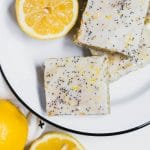 An aerieal view of a white and black plate filled with lemon poppy seed cookie bars topped with lemon glaze and poppy seeds and fresh lemons.