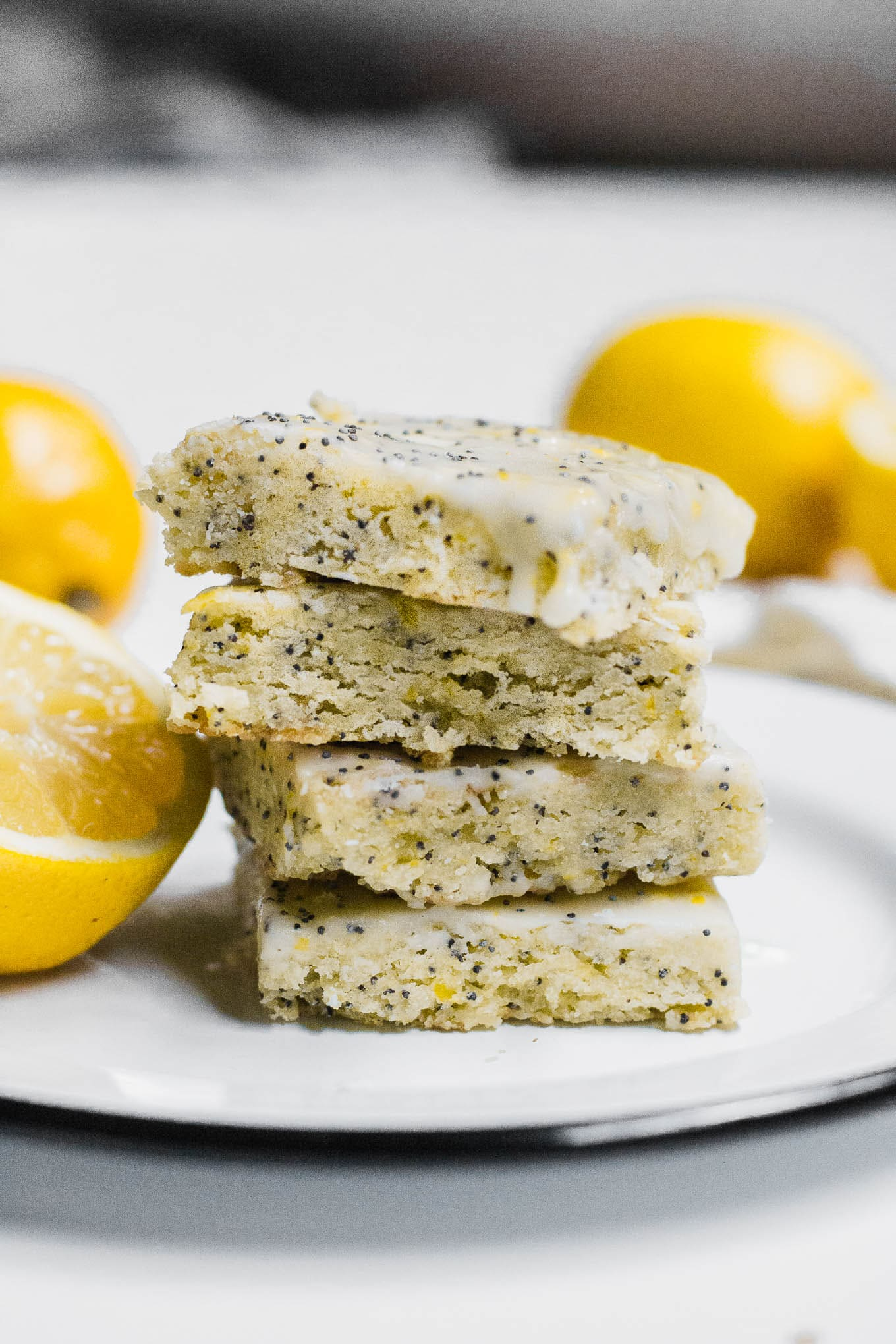 A front view of a stack of four gluten-free lemon poppy seed bars  with slices of lemon.