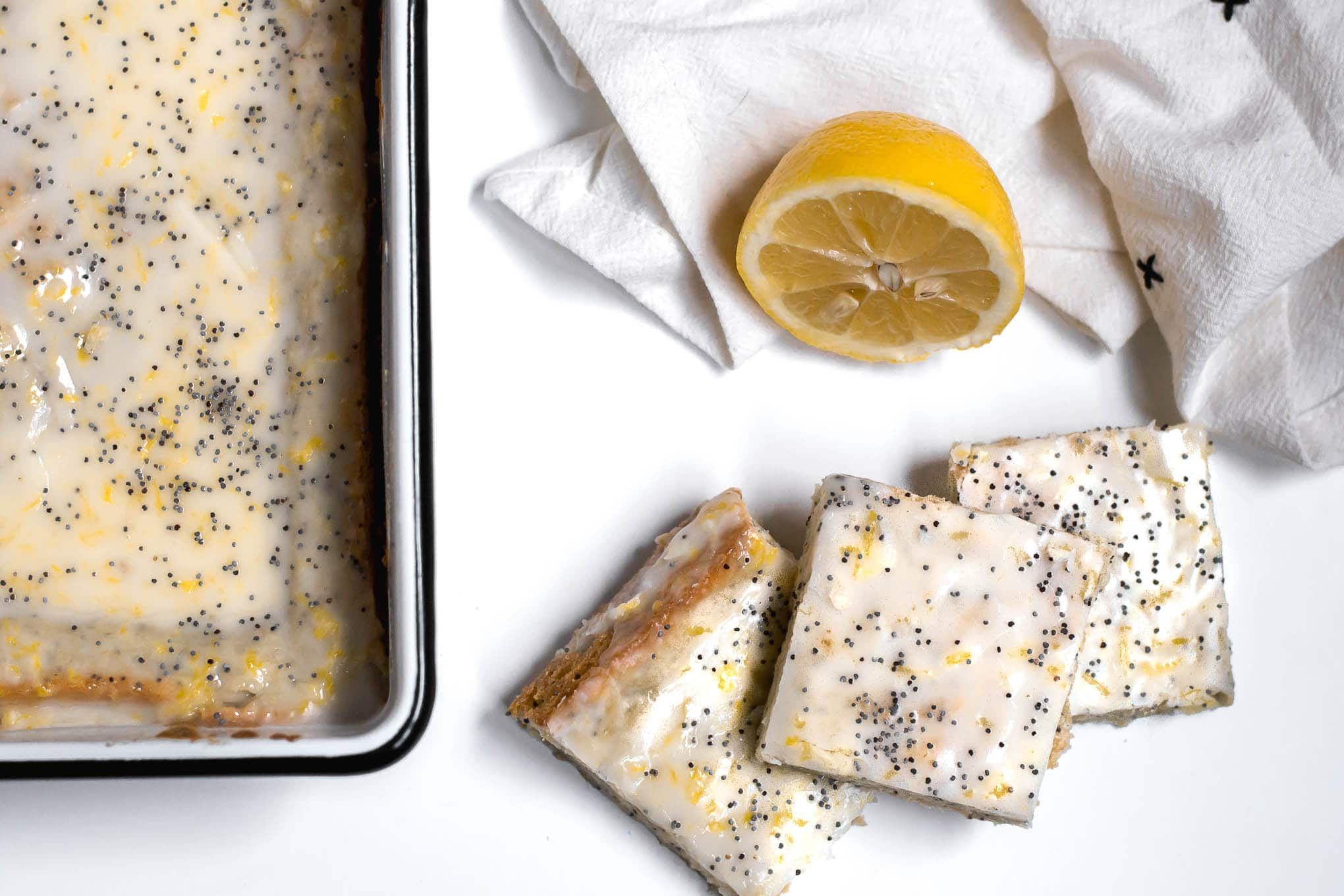 A pan of lemon poppy seed sugar cookie bars on a white table with slices of cookie bars on the table, a white and black napkin and half of a fresh lemon.