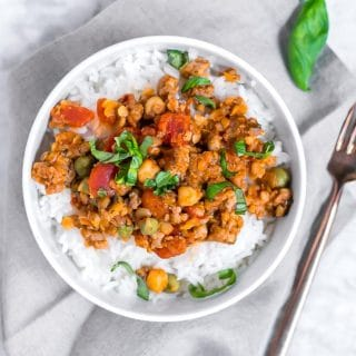 Italian sausage, lentil and chickpeas in a tomato sauce topped with basil in a bowl of white rice sitting on a gray napkin on a marble table with a gold fork on the side of it