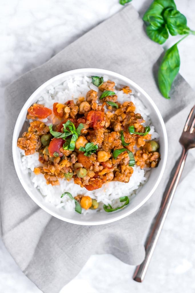 one pot garbanzo lentil and italian sausage - Italian sausage, lentil and chickpeas in a tomato sauce topped with basil in a bowl of white rice sitting on a gray napkin on a marble table with a gold fork on the side of it