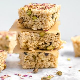 A stack of three gluten-free marshmallow treats made from rice cereal and topped with pistachios and rose petals on a marble table. Parchment paper squares separates each marshmallow treat. there are pistachios and rose petals scattered on the table.
