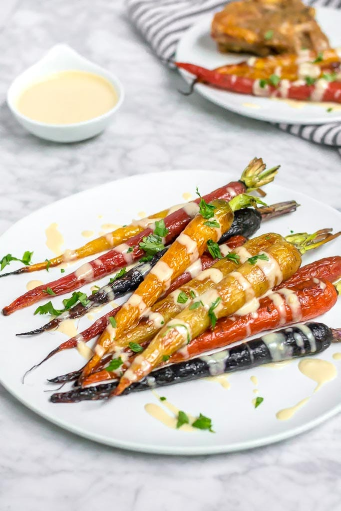 Multi-color roasted rainbow carrots on a white plate drizzled with a light and creamy lemon tahini sauce. A small bowl of sauce in the upper left corner. Roasted Rainbow Carrots with Lemon Tahini Sauce - Gluten-free, Dairy-free, Vegan - A Dash of Megnut