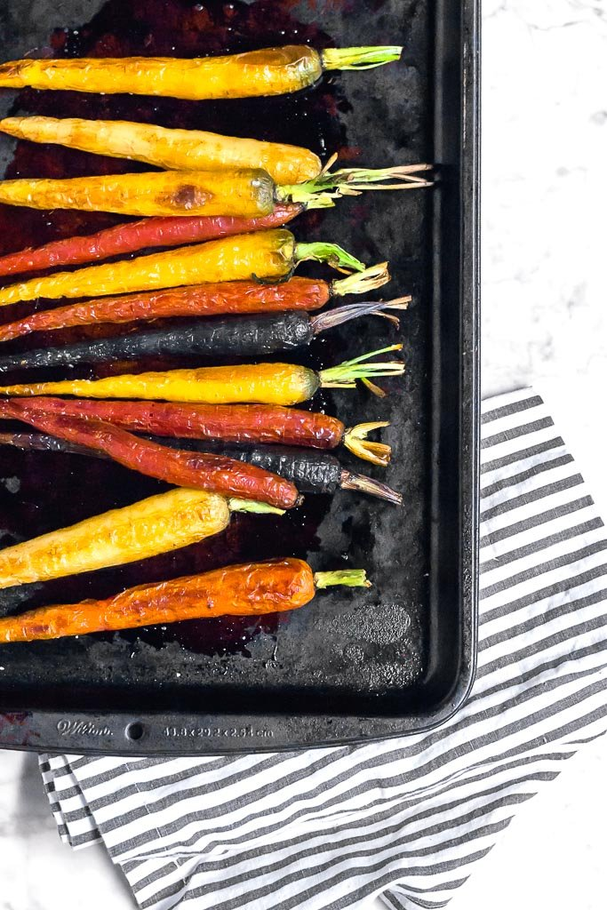A baking sheet with roasted multi-color rainbow carrots on it sitting on a marble table with a white and gray striped towel.