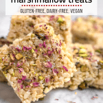 A stack of pistachio rose marhsmallow treats topped with edible rose petals, chopped pistachios and flaky sea salt
