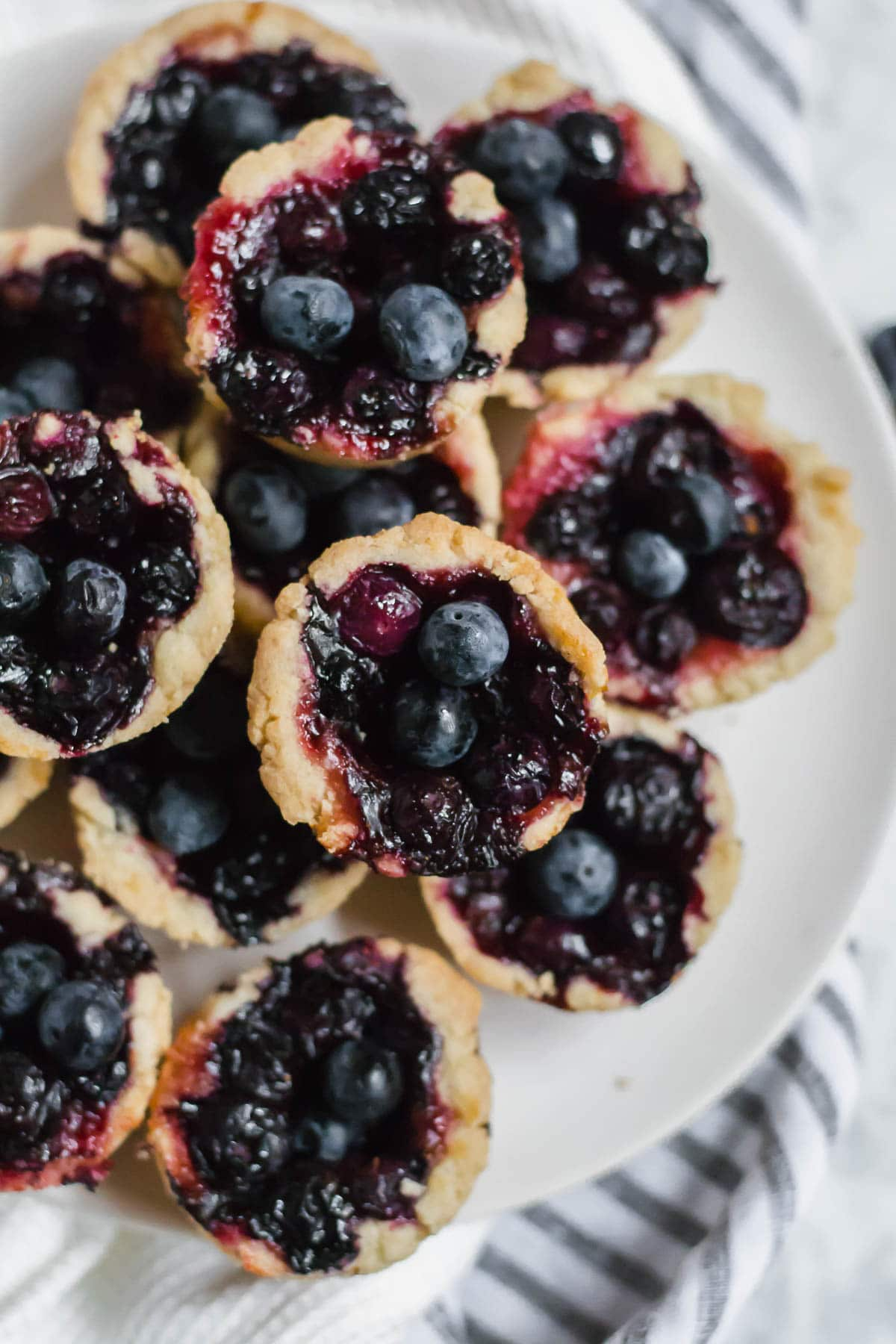 Aerial view of a plate of gluten-free mini blueberry tarts on a striped napkin.