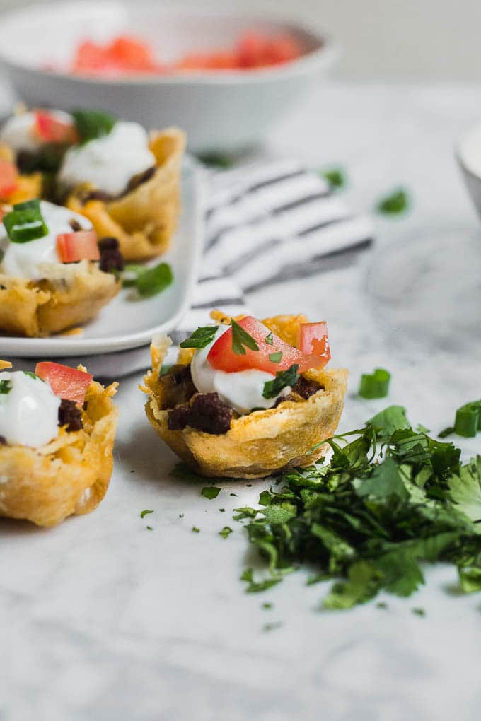 A few gluten-free mini taco bites with ground beef, sour cream, tomato, cheddar cheese on a marble table surrounded by toppings.