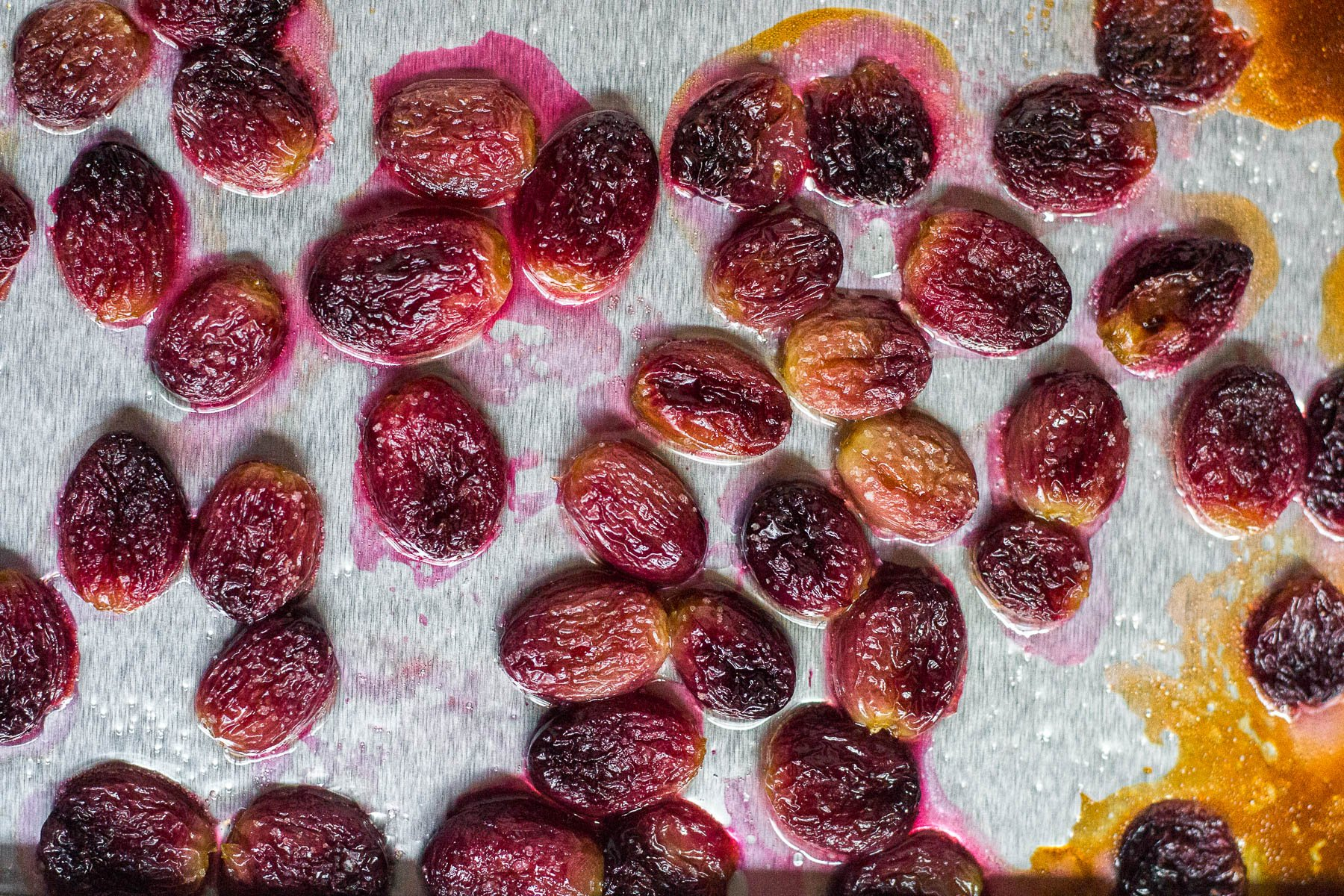 An aerial view of a baking sheet with roasted grapes tossed in oil and a pinch of sea salt.