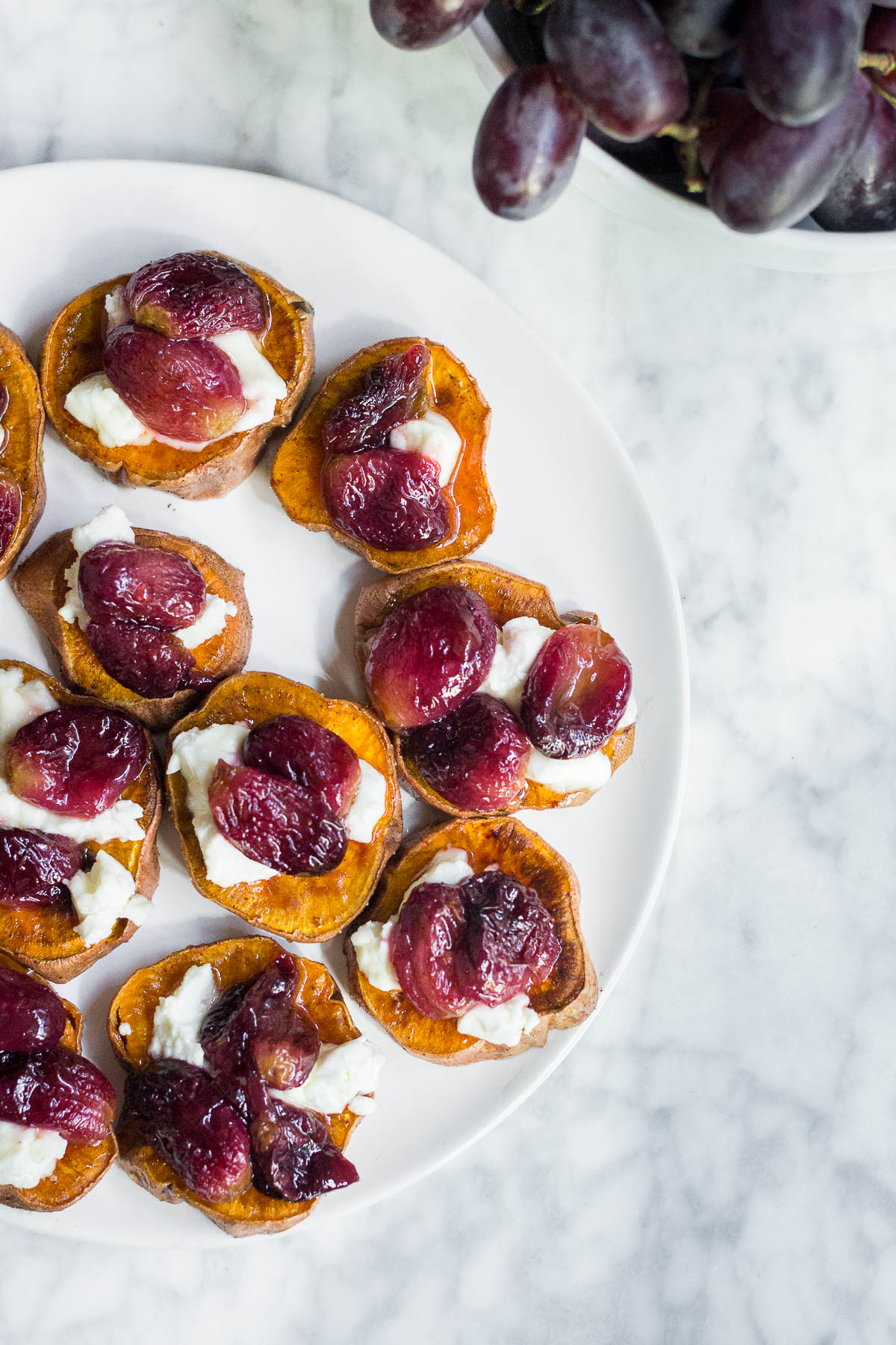Aerial view of a plate of sweet potato rounds with roasted grapes, goat cheese and honey and a bowl of fresh grapes