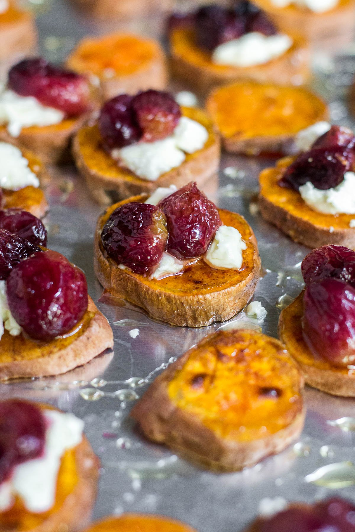 A baking sheet full of roasted sweet potato rounds topped with roasted grapes, crumbled goat cheese and honey.