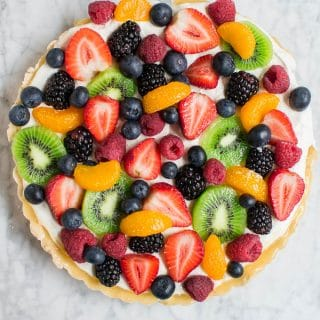 Aerial view of a round fruit tart with gluten-free shortbread crust and topped with blueberries, raspberries, strawberries, blackberries, kiwi and mandarin oranges