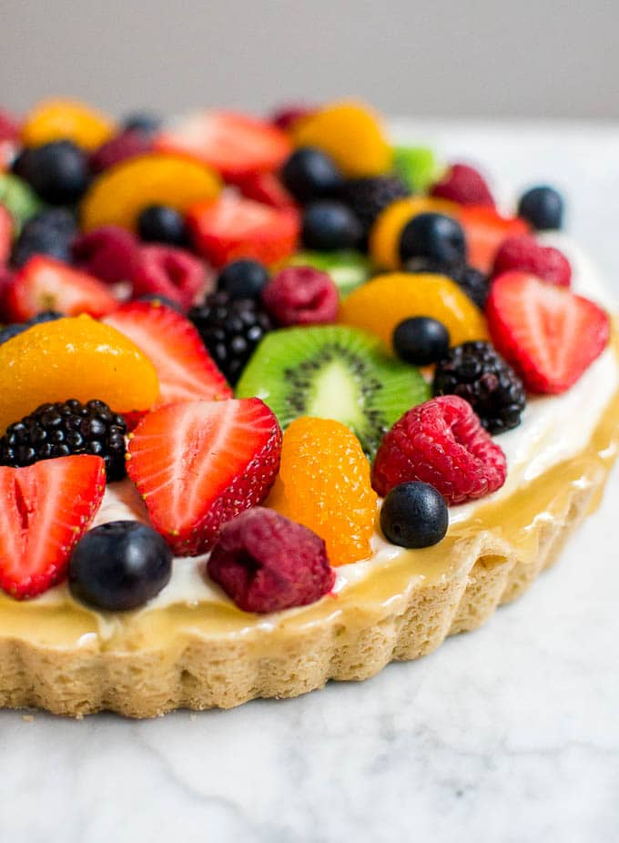 A photo of a gluten-free tart shell filled with lemon curd and fresh fruit.