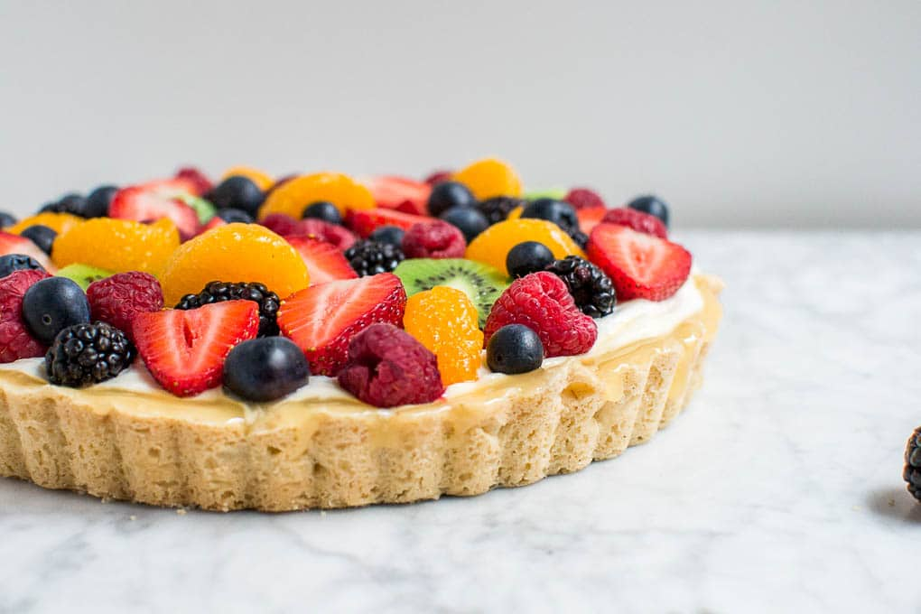 A straight on view of a shortbread crusted gluten-free fruit tart with berries, oranges, and kiwi.