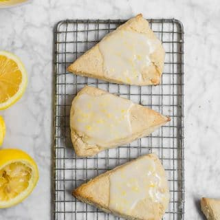 An aerial view of a rectangle baking cooling rack with three lemon scones with lemon glaze and a bowl of lemon curd, with lemon halves.