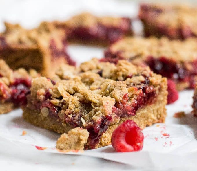 Straight on view of a raspberry crumb bar with raspberry filling and oat topping.