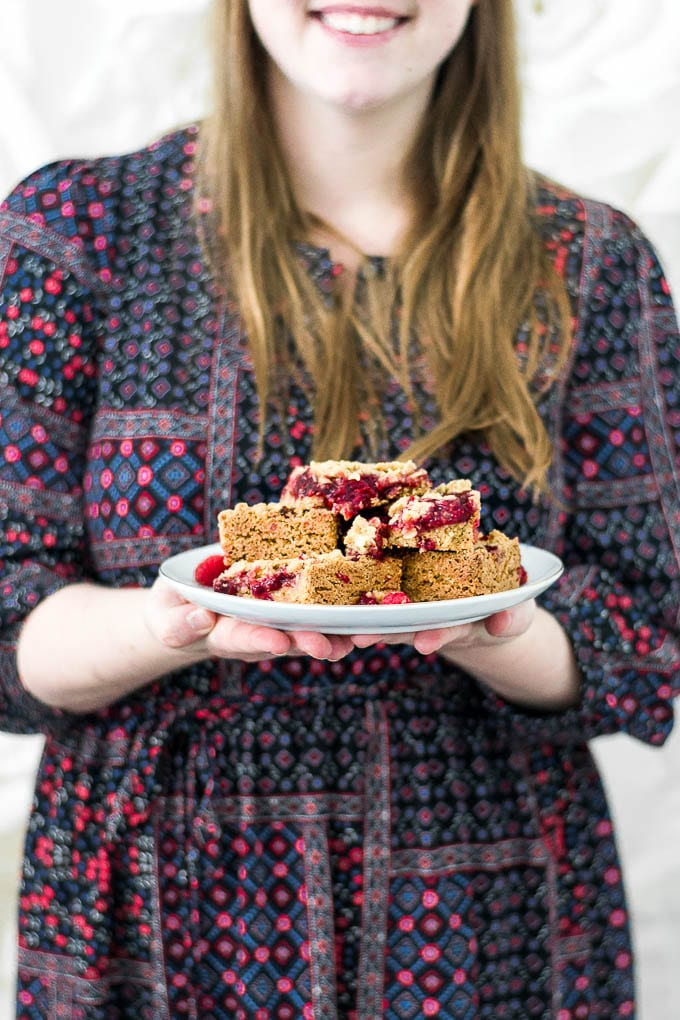 A straight on view of a woman holding a plate of gluten-free raspberry crumb bars.