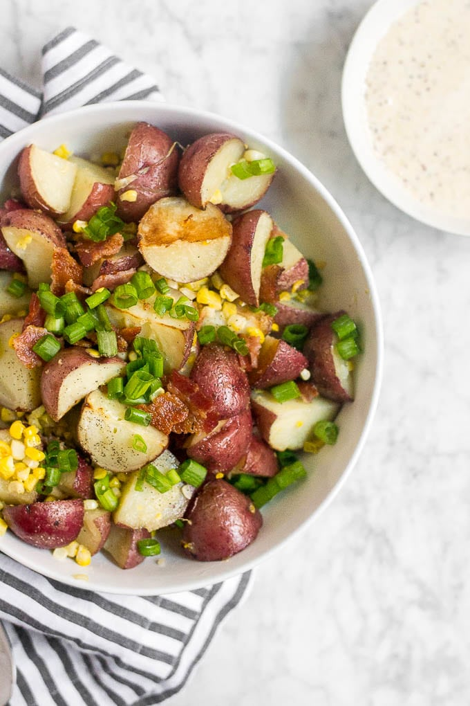 A bowl filled with potatoes, bacon, corn and green onion next to a smaller bowl filled with creamy mustard sauce ready to make potato salad.