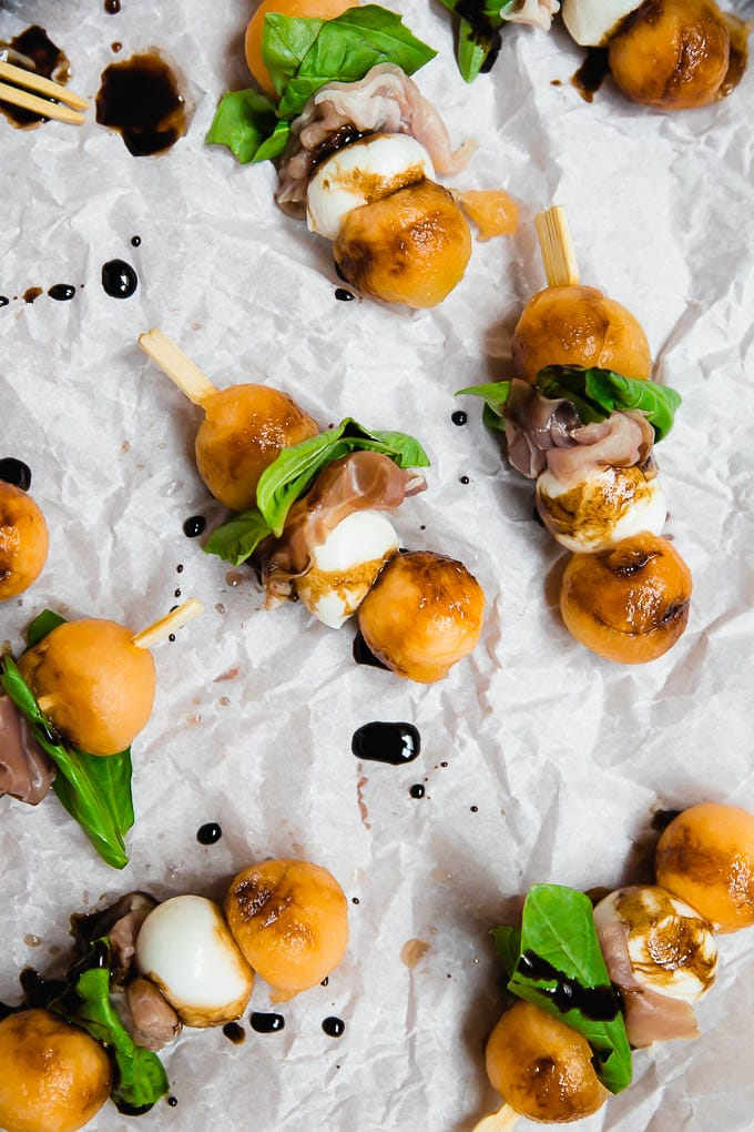 Aerial view of melon mozzarella balls prosciutto and basil on an appetizer skewer drizzled with balsamic vinegar glaze on white parchment paper