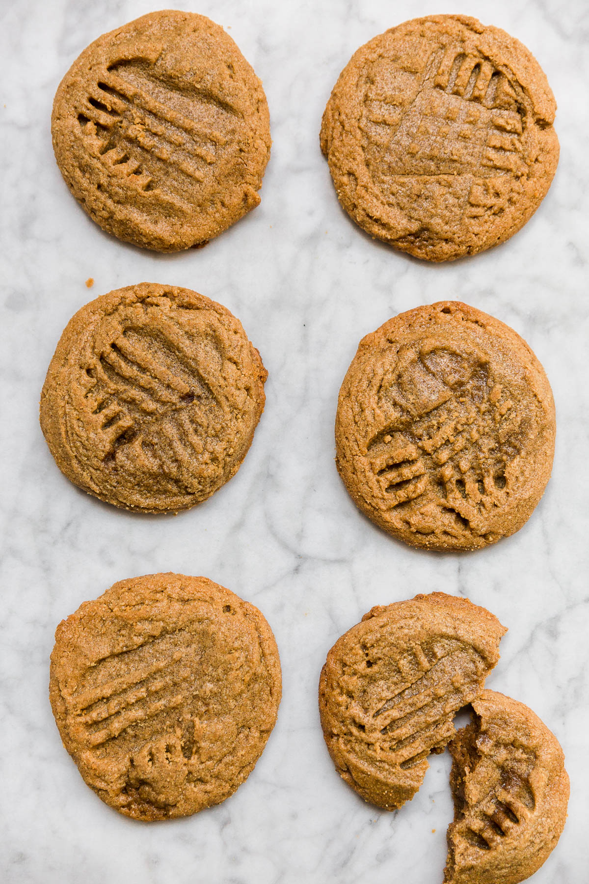 Aerial view of flourless peanut butter cookies in two rows with one cookie broken.
