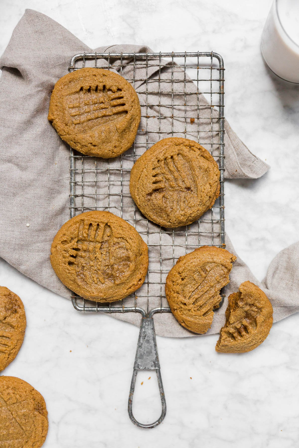 An aerial view of a cooling rack with 3-ingredient peanut butter cookies on a marble table with a gray napkin.