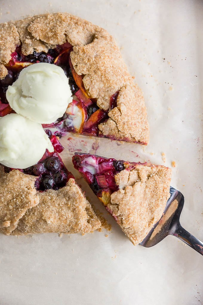 A rustic gluten-free vegan galette filled with blueberries, peaches, and rhubarb, topped with vanilla dairy-free ice cream with a wedge cut out of it on brown parchment paper.