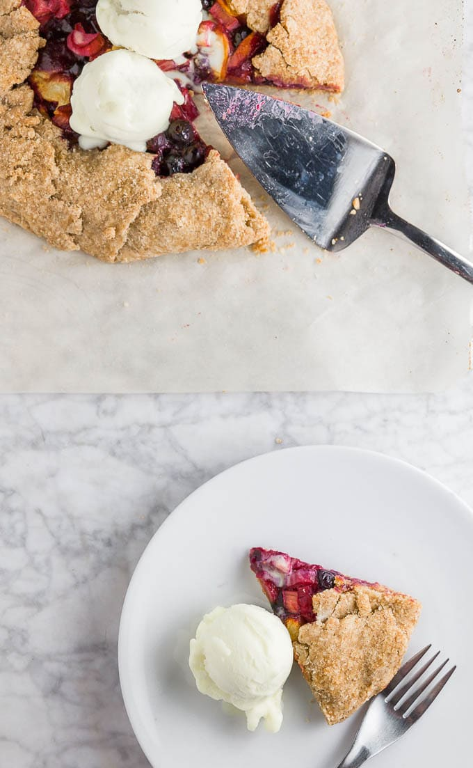 A gluten-free peach blueberry rhubarb galette on a marble table and a piece of galette on a white plate with a scoop of vanilla ice cream and a fork.