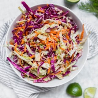 A white bowl containing cabbage dill slaw with red cabbage, green cabbage, carrots and dill with lime wedges on a table and fresh dill.