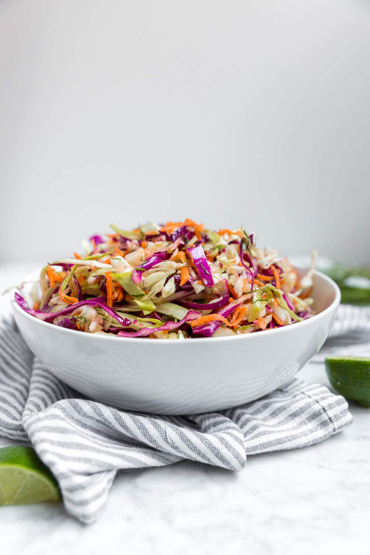 A straight on view of a white bowl containing cabbage carrot coleslaw with dill vinaigrette and lime wedges on a table.