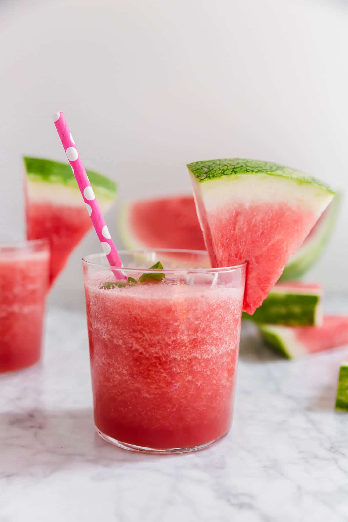 A short glass with watermelon rosé slushie with a watermelon wedge and pink polka dot straw.