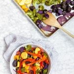 A sheet pan with rainbow vegetables that were roasted in the oven with a wooden spoon and a bowl with zucchini, tomatoes, broccoli, purple potatoes, bell peppers and carrots in it.