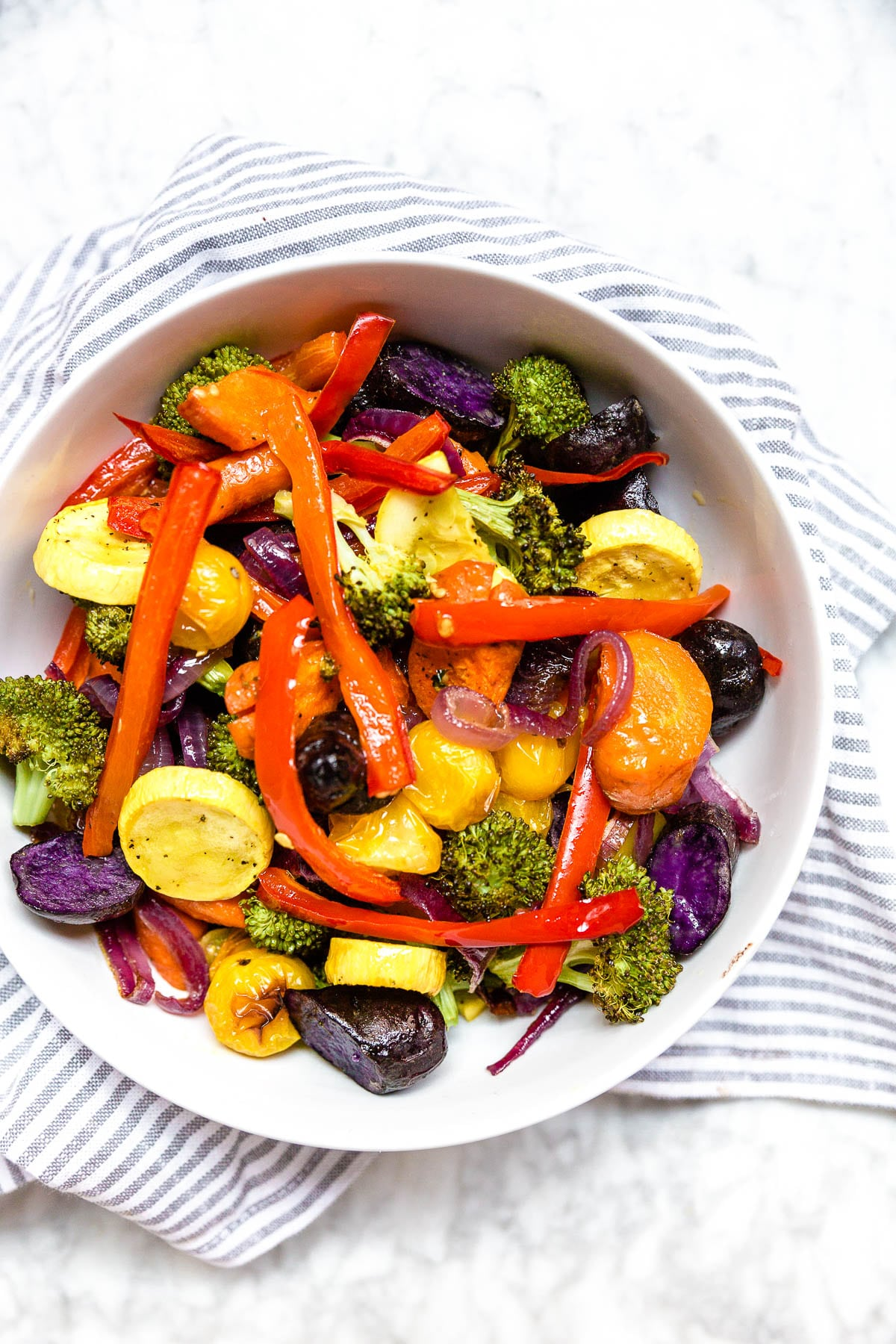 A bowl of mixed roasted vegetables in a rainbow of colors on a white table.