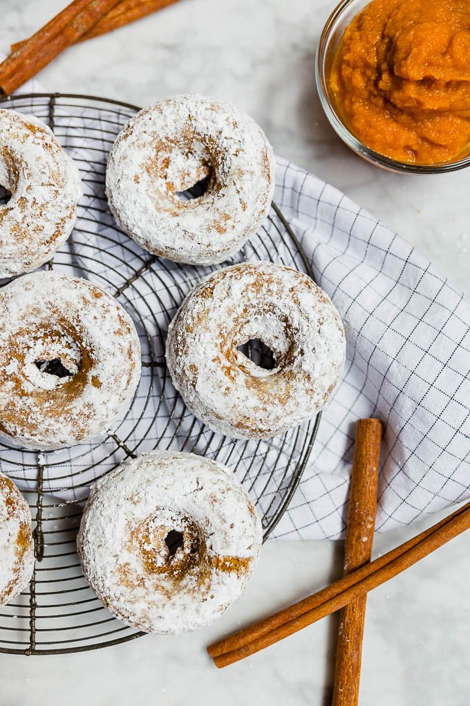 Baked pumpkin donuts rolled in powdered sugar with cinnamon sticks and pumpkin puree.