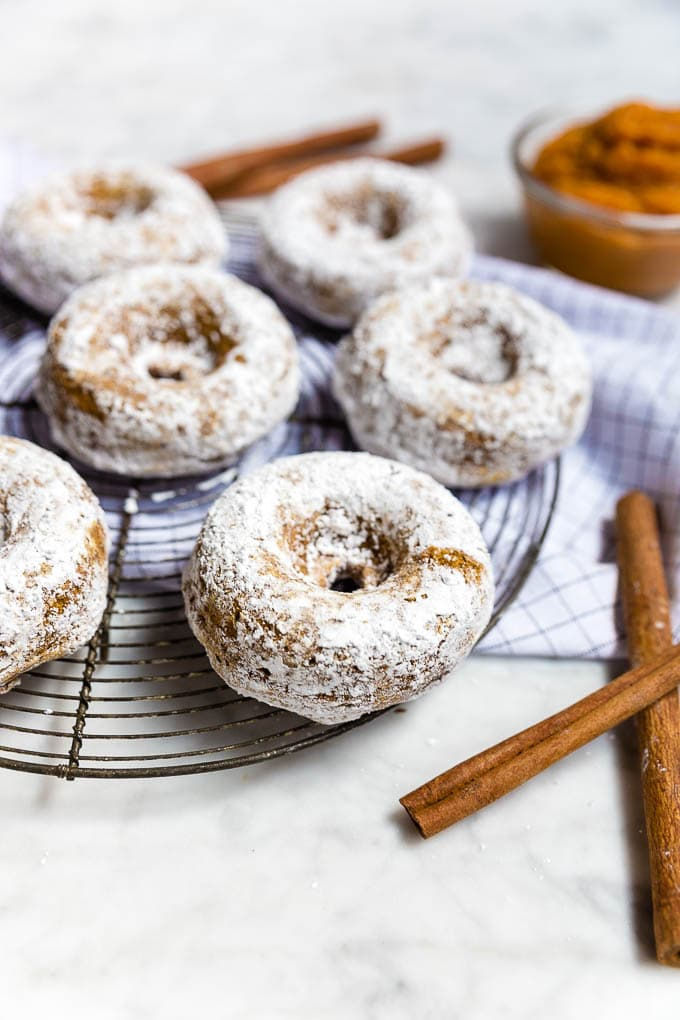 A wire rack of gluten-free vegan pumpkin donuts rolled in powdered sugar.