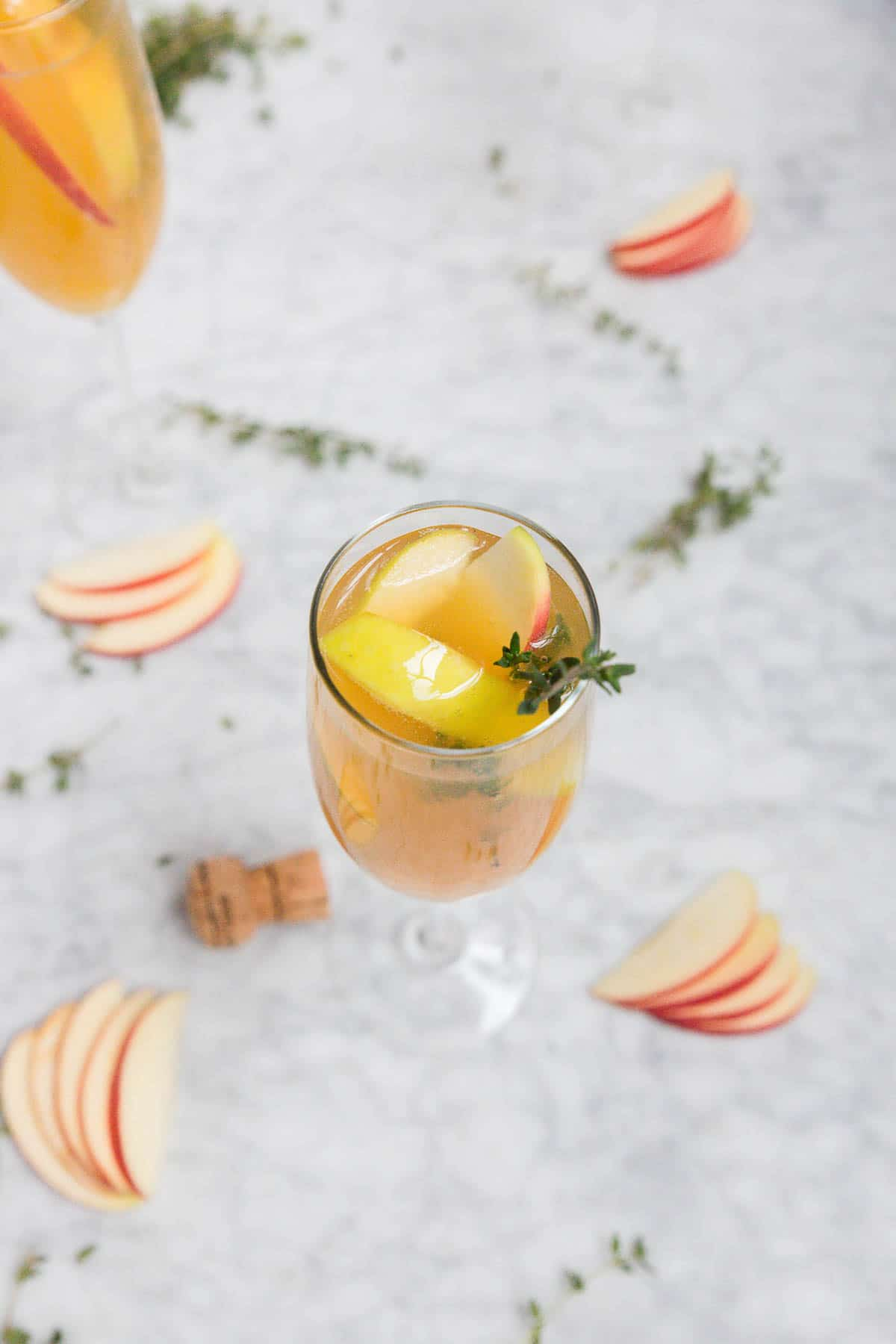 A glass of apple cider thyme mimosa cocktail with fresh apples and thyme sprigs