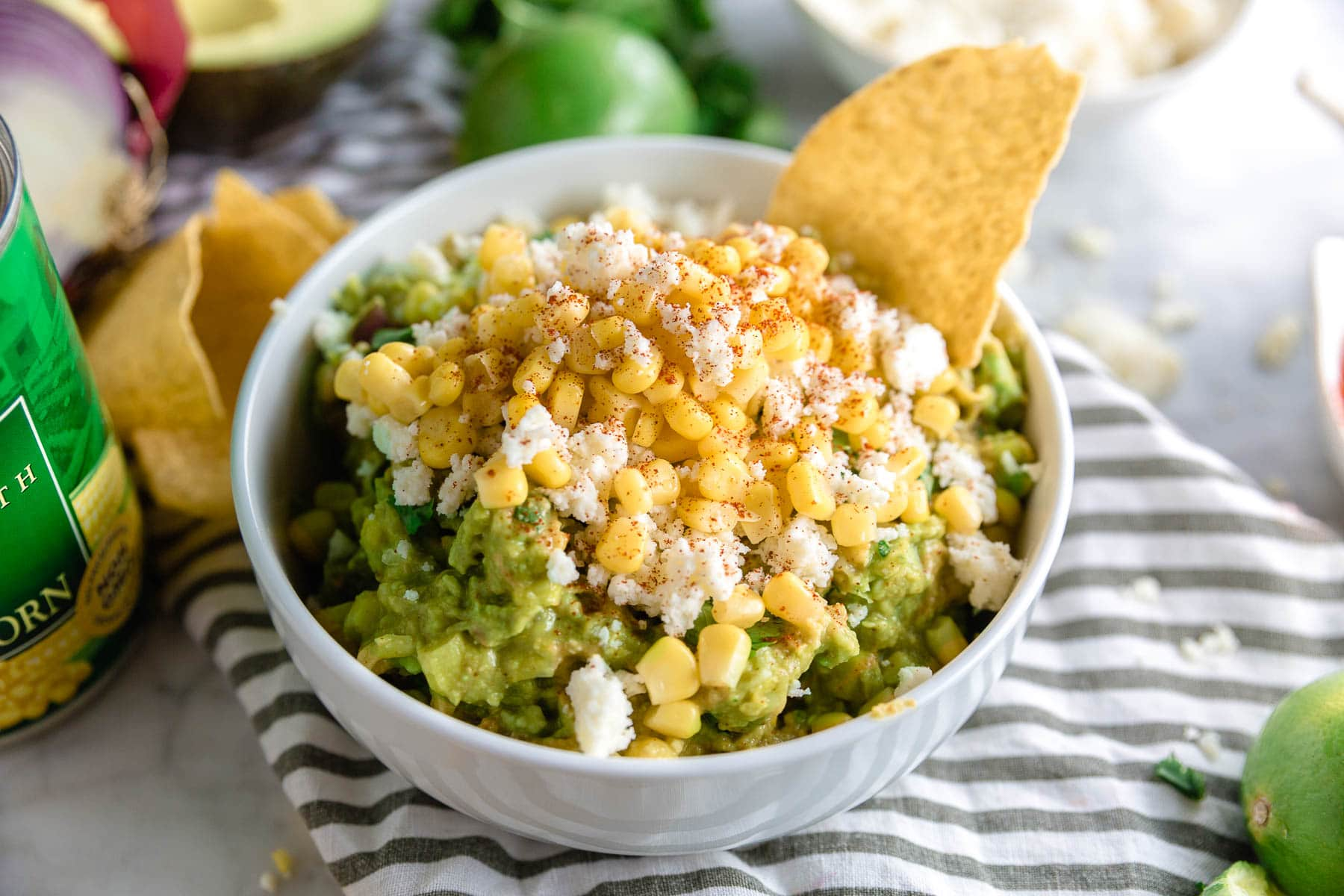 A bowl of corn and cotija cheese guacamole with a tortilla chip and a dusting of paprika on top.