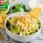 A bowl of guacamole with corn and cotija cheese with a corn tortilla chip in it.