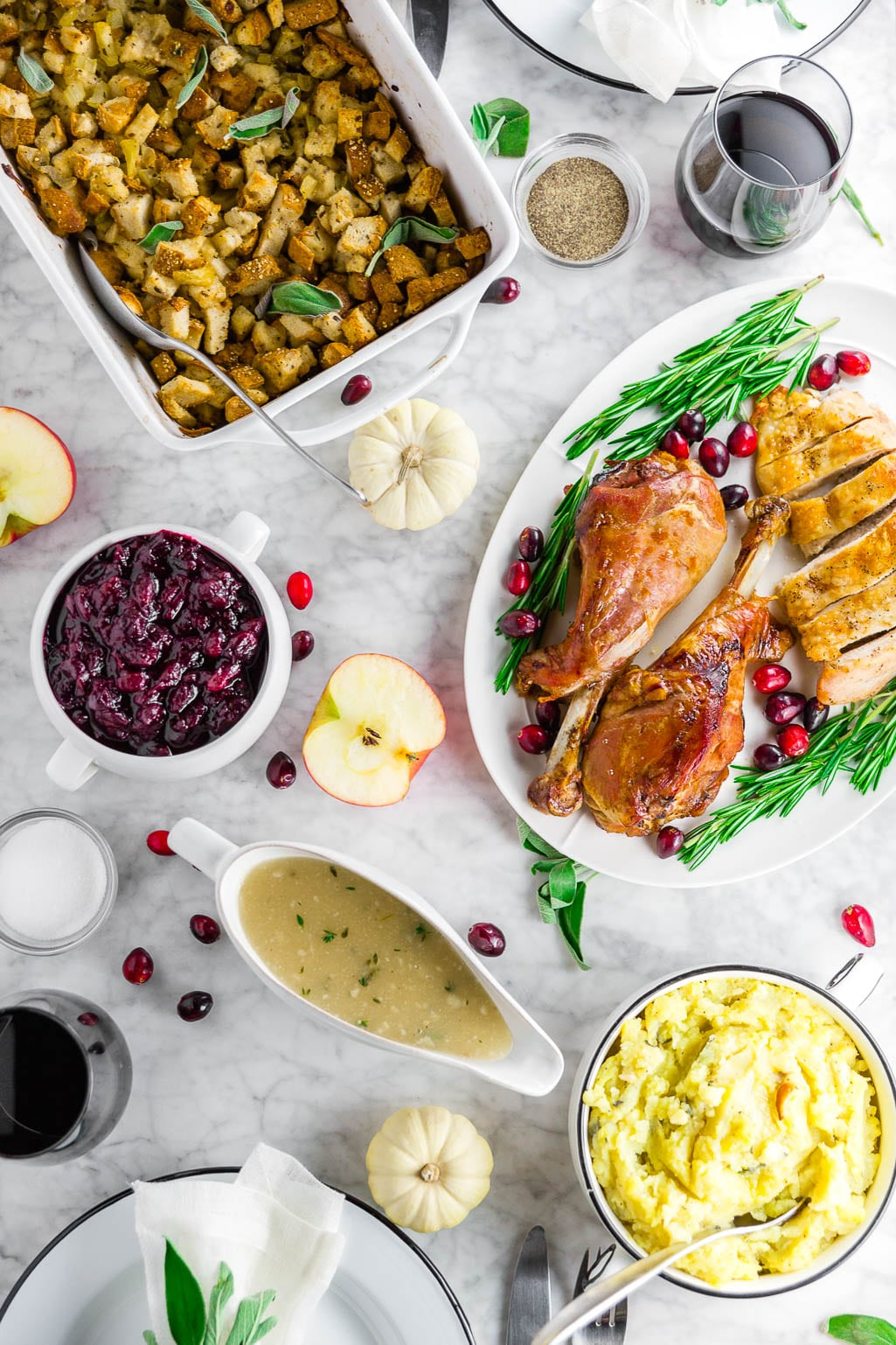 A white marble table with a Thanksgiving feast with gluten-free stuffing, turkey legs with cranberries and rosemary, cranberry sauce, gluten-free grave, a bowl of mashed potatoes, and two glasses of red wine with place settings.