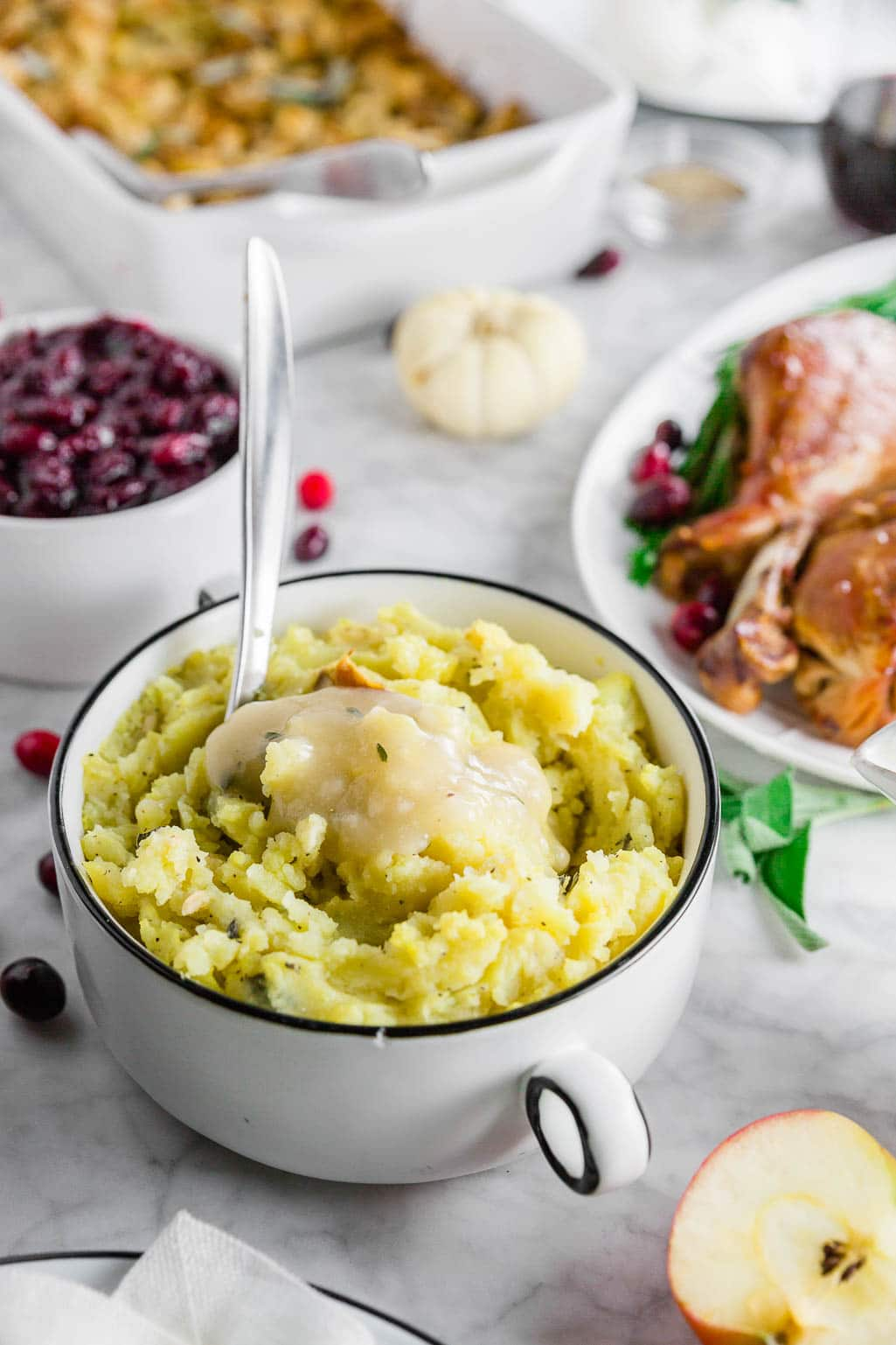 A gluten-free thanksgiving table with roasted garlic mashed potatoes, turkey, stuffing and cranberry sauce.