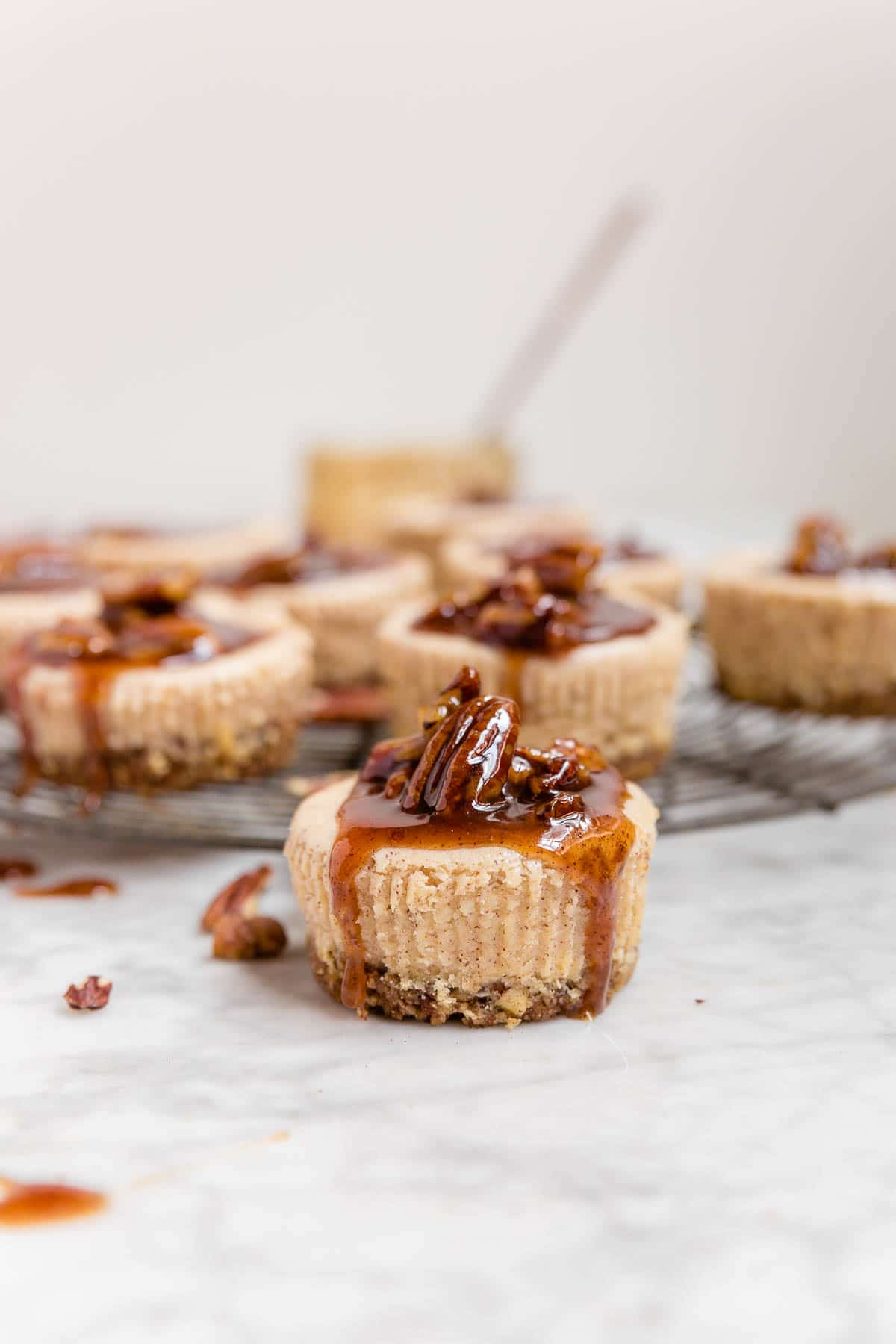 A mini pecan pie cheesecake with pecan pie caramel sauce dripping down the sides and a cooling rack with pecan pie cheesecakes in the background.